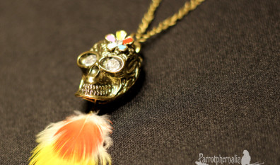 Brass Coloured Rhinestone Eyed Floral Skull Pendant with Yellow and Red Macaw Feathers